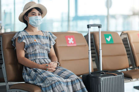 Young female wearing surgical face mask in airport terminal, protection Coronavirus disease (Covid-19) infection, Asian woman traveler sitting on chair. New Normal, social distancing and safety travel Reklamní fotografie