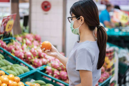 Asian woman wearing surgical face mask and holding orange fruit in supermarket or grocery, protect coronavirus inflection. Hygiene, new normal and life under covid-19 pandemic