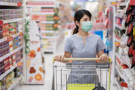 Young woman wearing protective face mask and shopping in grocery or department store protect coronavirus inflection. social distancing, new normal and life under covid-19 pandemic Foto de archivo