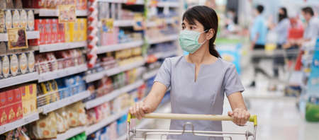 Young woman wearing protective face mask and  shopping in grocery or department store protect coronavirus inflection. social distancing, new normal and life under covid-19 pandemic