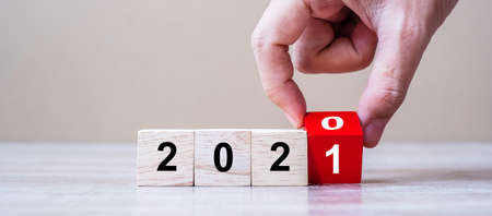Businessman hand flipping wooden cube blocks with 2020 change to 2021 number text on table background. New Year Resolution, strategy, plan, start, goal, business and holiday concepts