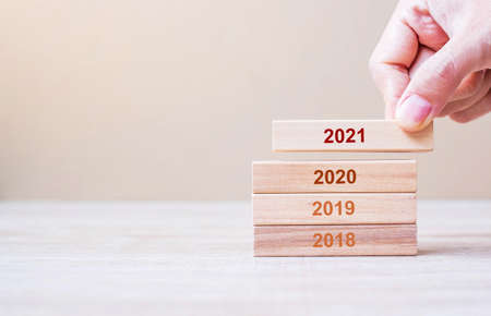 Businessman hand holding wooden cube with text 2021 number over 2020, 2019 and 2018 number on table background. Resolution, strategy, solution, goal, business and New Year holiday concepts