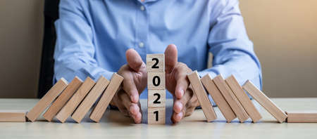 Businessman hand Stopping Falling of 2021 wooden Blocks. Business, Risk Management, Insurance, Resolution, strategy, solution, goal, New Year New You and happy holiday concepts Reklamní fotografie