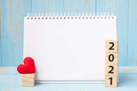 blank notebook and 2021 cubes with red heart shape decoration on blue wooden table background. New Year NewYou, Goal, Resolution, health, Love and Happy Valentine's day concept