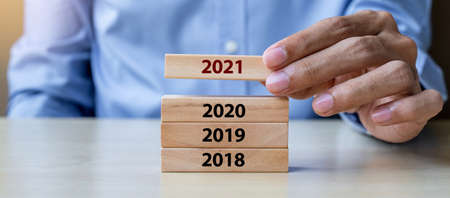 Businessman hand pulling 2021 wooden building blocks on table background. Business planning, Risk Management, Resolution, strategy, solution, goal, New Year New You and happy holiday concepts