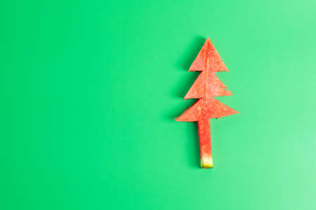 Christmas tree of watermelon on green background. Merry Xmas and happy New Year party, Celebrating and dessert concept