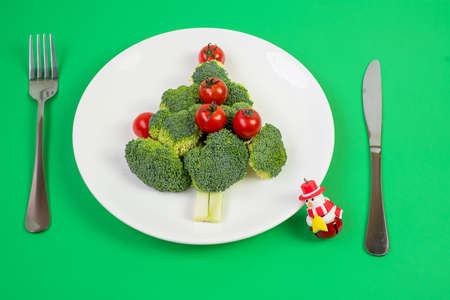 Christmas tree of organic vegetables on white plate; Broccolis and tomatoes with fork and knife on green background. Merry Xmas and happy New Year party, New You, Healthy food and vegetarian concept Stock Photo