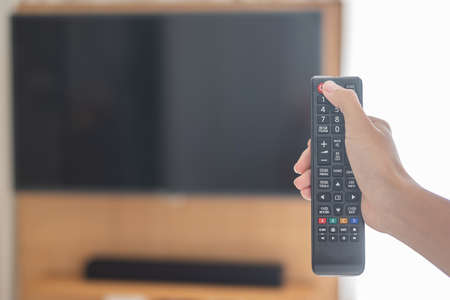 hand using remote controller for adjust Smart TV inside the modern room at home or luxury hotel