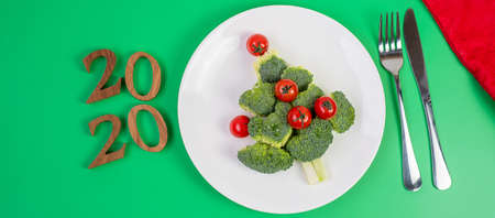 2020 Christmas tree of vegetables on white plate; Broccolis and tomatoes with fork and knife on green background. Merry Xmas and happy New Year party, New You, Healthy food and vegetarian concept