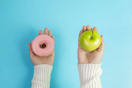 woman holding green apple and pink donut, female choose between fruit is Healthy food and sweet is unhealthy junk foods. Dieting, obesity, eating lifestyle and nutrition concept