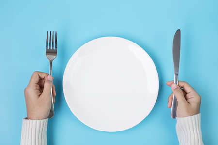 Hands holding knife and fork above white plate on blue background., dieting, weight loss, dining and kitchenware concept