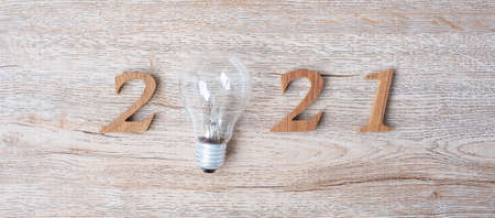2021 Happy New year with lightbulb and wooden number on table. New Start, Idea, Creative, Innovation, Resolution, Solution, Strategy, Goals and Mission concept