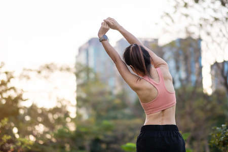 Young adult female in pink sportswear stretching muscle in the park outdoor, sport woman warm up ready for running and jogging in morning. wellness, fitness, exercise and work life balance concepts