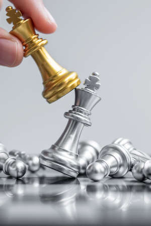 businessman hand moving gold Chess King figure and Checkmate enermy or opponent during chessboard competition. Strategy, Success, management, business planning, interruption and leadership concept