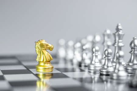 Gold Chess Knight (horse) figure on Chessboard against opponent or enemy. Strategy, Conflict, management, business planning, tactic, politic, communication and leader concept