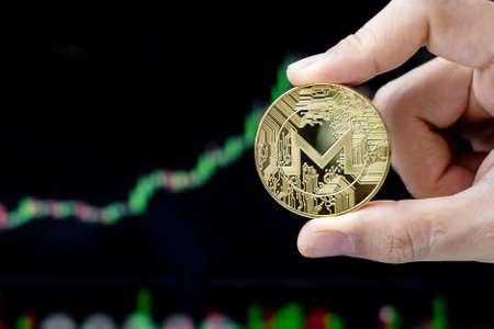 Golden Monero (XMR) cryptocurrency coin with candle graph background, Crypto is Digital Money within the blockchain network, is using technology and online internet exchange