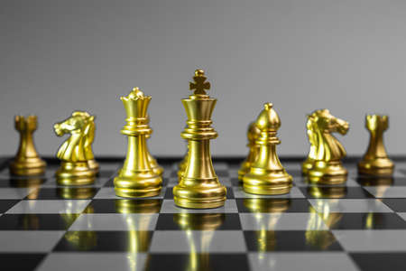 Gold Chess figure team (King, Queen, Bishop, Knight, Rook and Pawn) on Chessboard against opponent during battle. Strategy, Success, management, business planning, think, education and leader concept