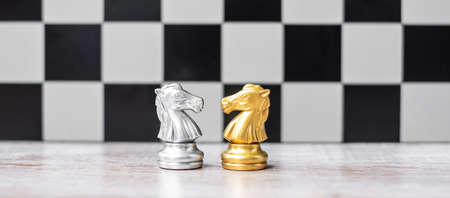 Gold and silver Chess Knight (horse) figure on Chessboard against opponent or enemy. Strategy, Conflict, management, business planning, tactic, politic, communication and leader concept