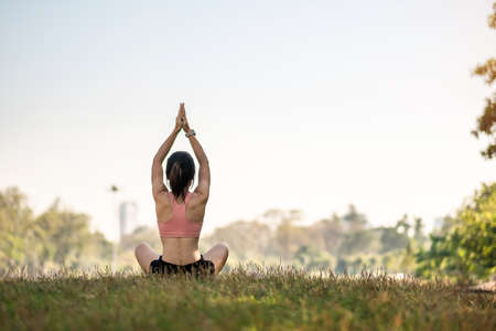Young adult female in sportswear doing Yoga in the park outdoor, healthy woman sitting on grass and meditation with lotus pose in morning. wellness, fitness, exercise and work life balance concepts