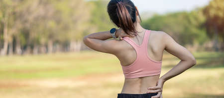 Young fitness woman holding her sports injury neck, muscle painful during training. Asian runner female having body problem after exercise outside in summer