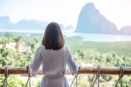 happy woman in bathrobe stretching after waking up and enjoy Phang Nga bay view point, Tourist relaxing in tropical resort at Samet Nang She, near Phuket in Thailand. Travel summer vacation concept Standard-Bild