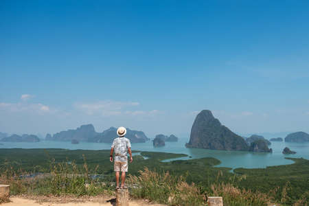 Happy traveler man enjoy Phang Nga bay view point, alone Tourist standing and relaxing at Samet Nang She, near Phuket in Southern Thailand. Southeast Asia travel, trip and summer vacation concept