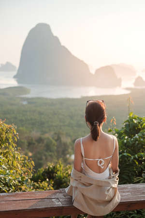 Happy traveler woman enjoy Phang Nga bay view point, alone Tourist sitting and relaxing at Samet Nang She, near Phuket in Southern Thailand. Southeast Asia travel, trip and summer vacation concept