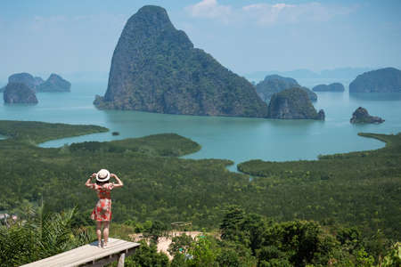 Happy traveler woman enjoy Phang Nga bay view point, alone Tourist standing and relaxing at Samet Nang She, near Phuket in Southern Thailand. Southeast Asia travel, trip and summer vacation concept