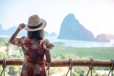 Happy traveler woman enjoy Phang Nga bay view point, alone Tourist relaxing at Samet Nang She, near Phuket in Southern Thailand. Southeast Asia travel, trip and summer vacation concept