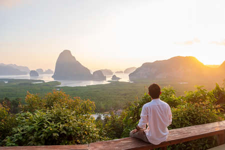 Happy traveler man enjoy Phang Nga bay view point, alone Tourist sitting and relaxing at Samet Nang She, near Phuket in Southern Thailand. Southeast Asia travel, trip and summer vacation concept Standard-Bild