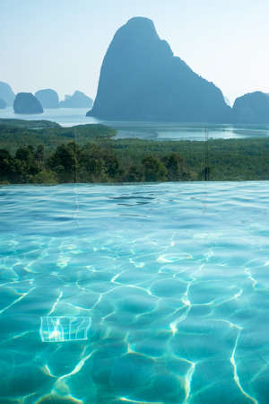 luxury pool hotel against Phang Nga bay background, Tourist relaxing at Samet Nang She, near Phuket in Southern Thailand. travel, trip and summer vacation Editorial
