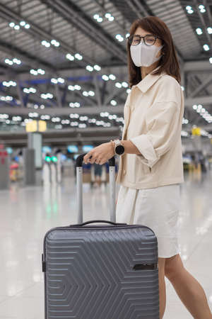 Young female wearing face mask with luggage checking flight time in airport, protection disease infection, Asian woman traveler ready to travel. New Normal and travel