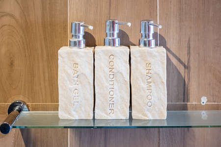 Toiletries bottles in bathroom at luxury hotel or modern home. shower container set, body shower gel, shampoo and hair conditioner in ceramic ware with wooden wall background