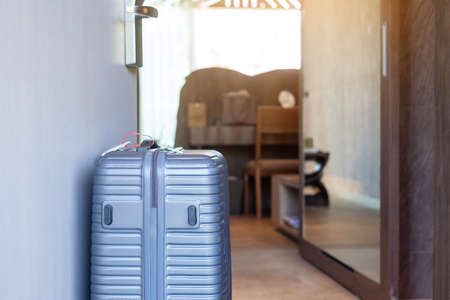Grey Luggage in modern hotel room after door opening. Time to travel, journey, trip and vacation concepts