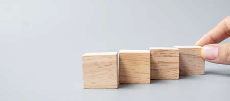 Businessman hand placing or pulling wooden block on the building. Business planning, Risk Management, Solution and strategy Concepts