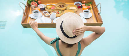Happy young woman in green swimsuit having Floating Breakfast tray in luxury pool hotel, girl with hat enjoy in tropical resort. Relaxing, Exotic summer travel, holiday, vacation and tropical