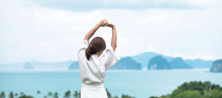 happy woman in bathrobe stretching after waking up and enjoy Ocean view, Tourist relaxing in tropical resort. summer travel, holiday and vacation concept Imagens