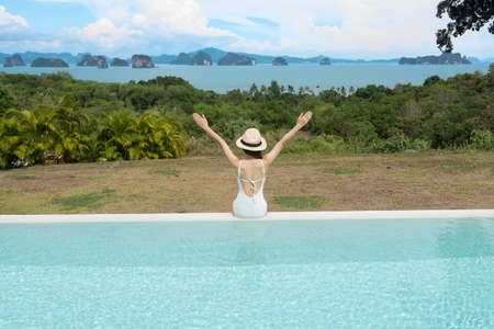 Happy woman in white swimsuit swimming in luxury pool hotel against beautiful view, young female with hat enjoy in tropical resort. Relaxing, summer travel, holiday and vacation concept Imagens
