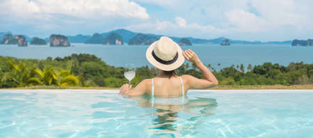 Happy woman in white swimsuit drinking wine in luxury swimming pool hotel against beautiful view, young female with hat enjoy in tropical resort. Relaxing, summer travel, holiday and vacation concept