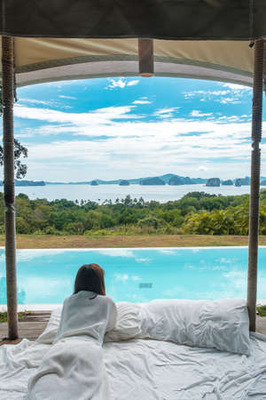 Happy woman traveler enjoy Beautiful ocean view, Tourist relaxing in tropical luxury resort with swimming pool. Leisure, travel and summer vacation concept