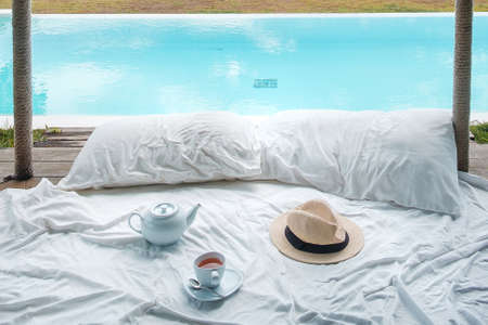 Traveler hat, hot tea cup and teapot on white bed against Beautiful ocean view background, Tourists relaxing in tropical resort with swimming pool. travel summer, vacation and freelance concept Imagens