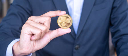 Businessman hand holding golden Ripple (XRP) cryptocurrency coin, Crypto is Digital Money within the blockchain network, is exchanged using technology and online internet exchange. Financial concept Imagens