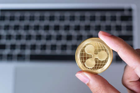 Businessman hand holding golden Ripple (XRP) cryptocurrency coin over keyboard laptop,. Crypto is Digital Money within the blockchain network Imagens