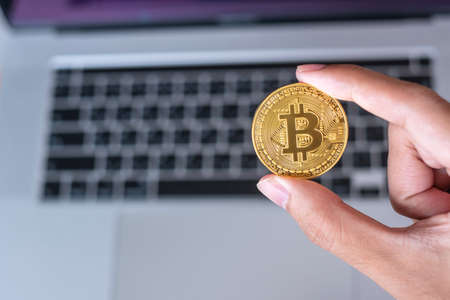 Businessman hand holding golden Bitcoin (BTC) cryptocurrency over laptop keyboard, Crypto is Digital Money within the blockchain network, is exchanged using technology and online exchange concept