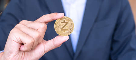 Businessman hand holding golden ZCASH (ZEC) cryptocurrency coin, Crypto is Digital Money within the blockchain network, is exchanged using technology and online internet exchange. Financial concept Imagens