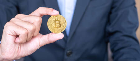 Businessman hand holding golden Bitcoin (BTC) cryptocurrency, Crypto is Digital Money within the blockchain network, is exchanged using technology and online internet exchange. Financial concept