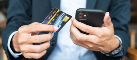 Businessman in suit holding credit card and using touchscreen smartphone for online shopping while making orders in the cafe or office .business, technology, ecommerce and online payment concept