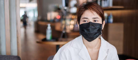 Woman wearing protective medical face mask in cafe, prevent virus Imagens