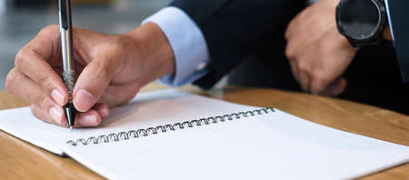 Businessman in suit writing something on notebook in office or cafe, hand of man holding pen with signature on paper report. business concepts