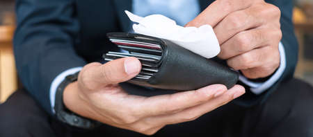 Businessman in suit cleaning money wallet by wet wipes tissue and alcohol disinfectant at office or cafe, protection coronavirus (Covid-19) infection. New Normal and Clean surface concept Imagens